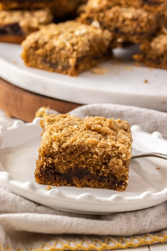 A piece of crumb cake on a small plate with more in the background