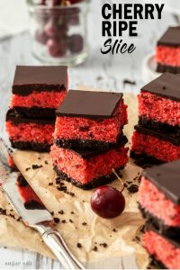 A stack of 2 cherry ripe slices, on a piece of parchment paper, surrounded by chocolate crumbs. A glass of cherries in the background