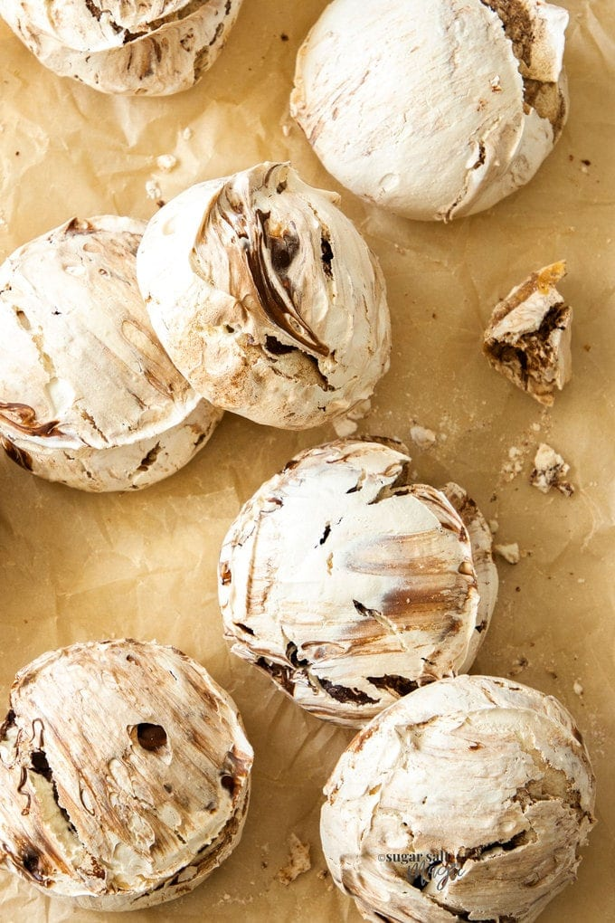 7 chocolate meringues on a sheet of brown baking paper