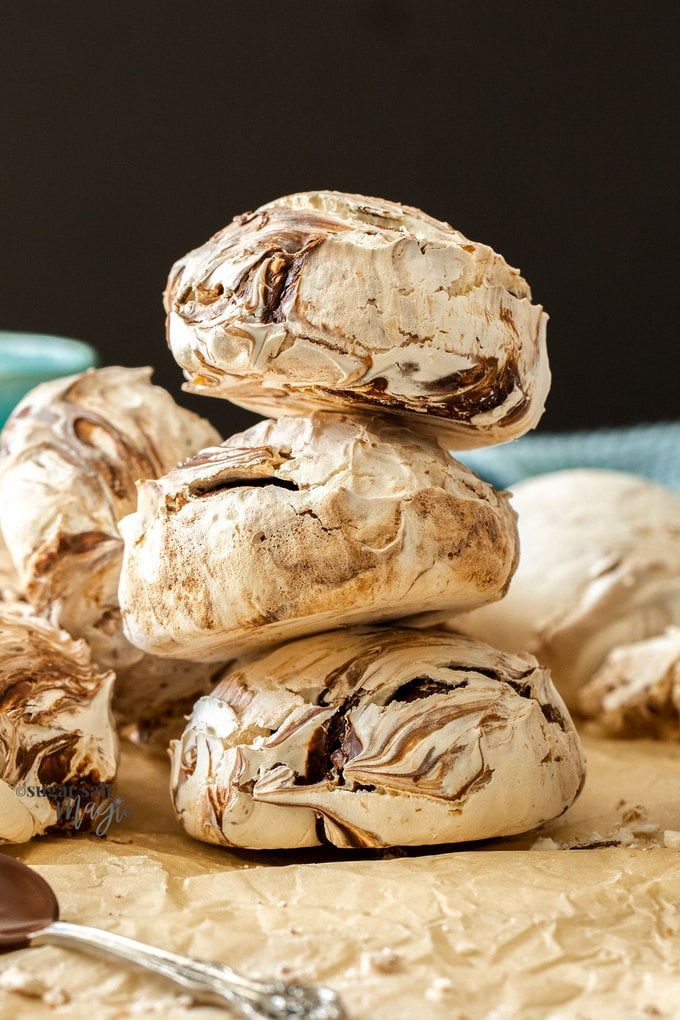 A stack of 3 large chocolate meringues on brown baking paper