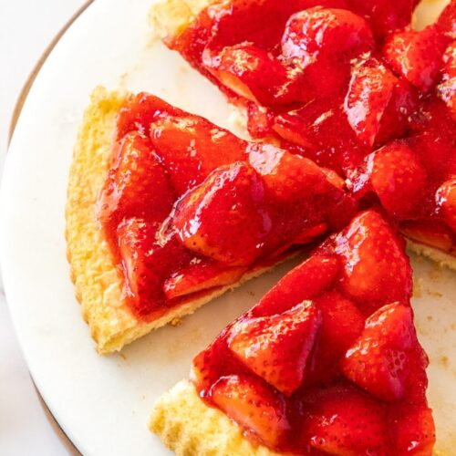 Top down view of 3 slices of strawberry flan on a white marble platter.
