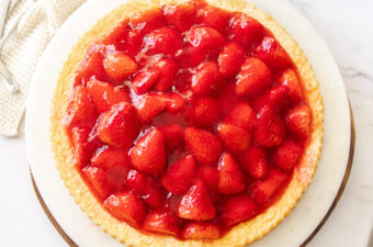 Top down view of a strawberry flan on a marble platter with strawberries scattered around