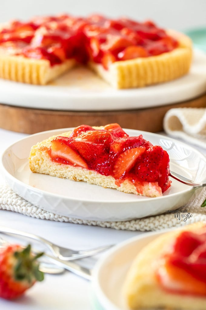 A slice of strawberry flan on a white plate, the rest of the tart sits in the background on a marble platter.