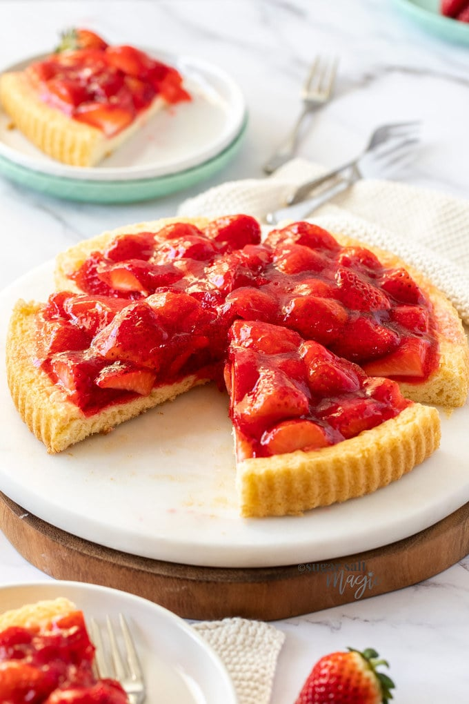 A strawberry tart with a light sponge base sitting on a marble platter with some slices cut out of it.