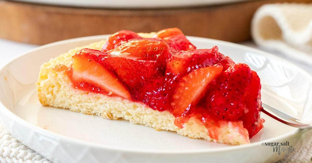 A slice of strawberry flan on a white plate.