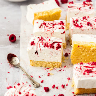8 squares of marsmallow slice on a crumpled piece of white baking paper. freeze dried raspberries scattered around and a spoon covered in jam