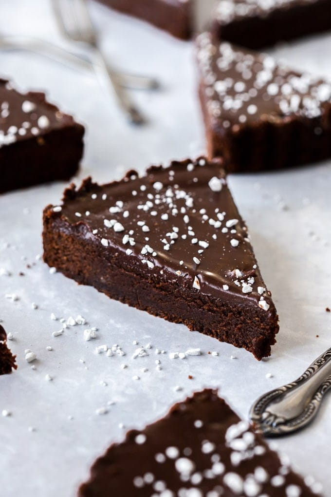 Closeup of a slice of chocolate brownie tart with more pieces around it