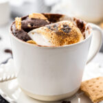 A white cup on a saucer filled with chocolate cake and toasted marshmallow. It sits on a grey crocheted napkin