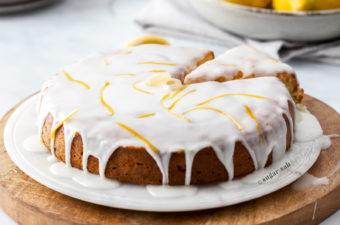A lemon cake drizzled with white icing on a marble platter and wooden board. Lemons in the background.