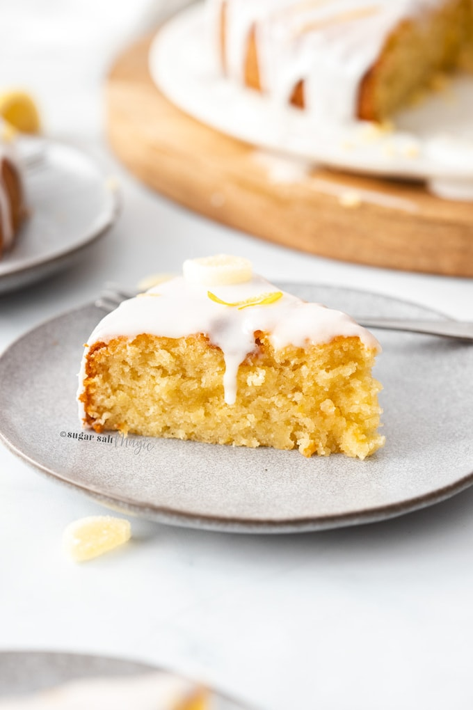 A slice of flourless lemon cake on a grey plate with a white icing drizzle down.