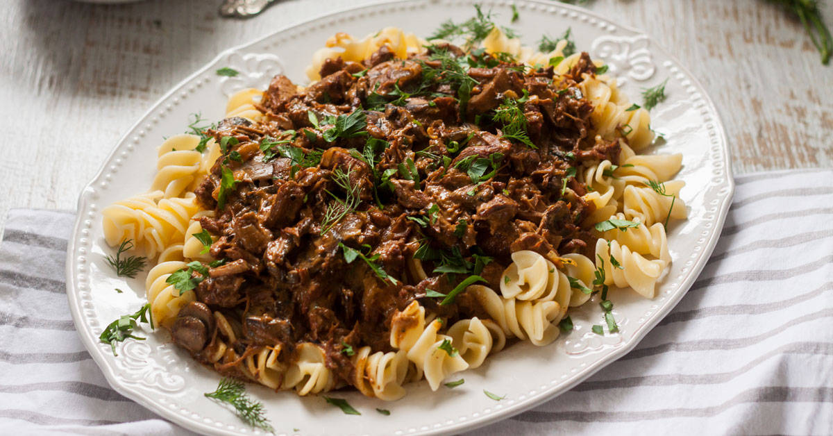 A large white plate filled with pasta and beef stroganoff on top of a striped tea towel