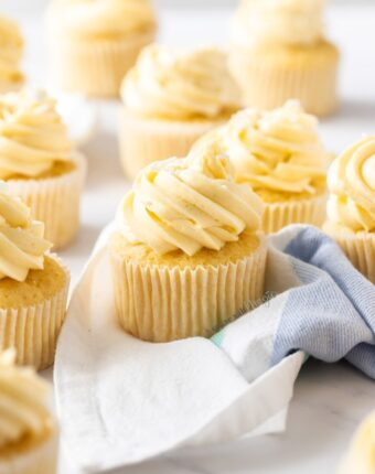 A batch of vanilla cupcakes on a marble surface. One is sitting on a white & blue tea towel.
