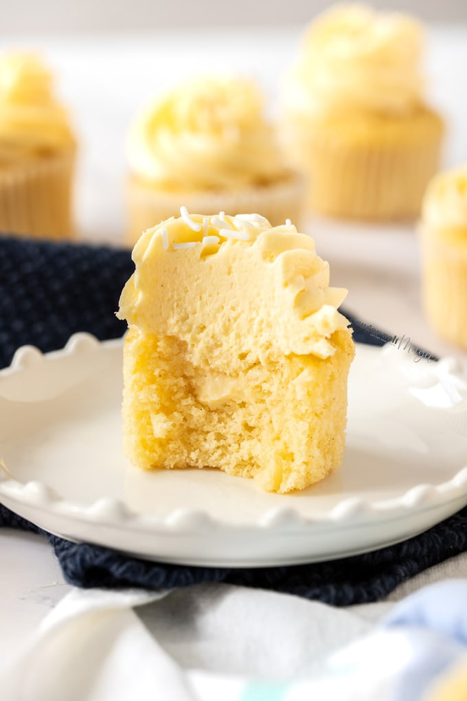 A vanilla cupcake, cut open to reveal a filling of creme patissiere. It sits on a white plate