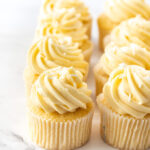 8 vanilla cupcakes lined up close together on a marble surface