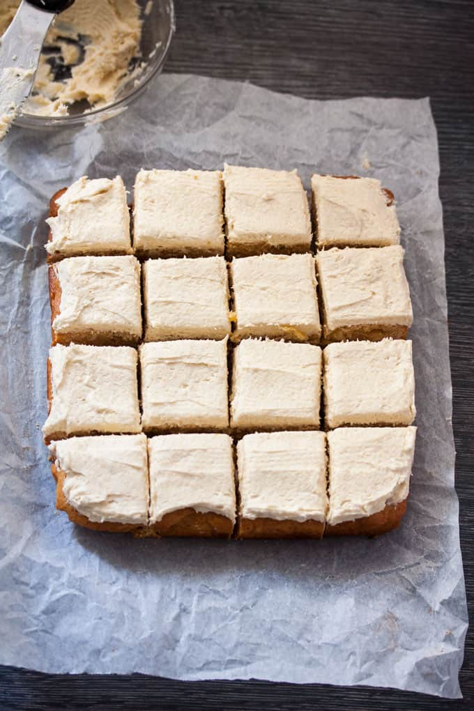 Top down view of 16 squares of frosted blondies on a sheet of baking paper, the frosting bowl in the background.