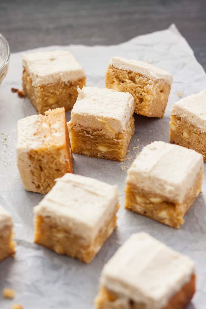 9 frosted blondies on a sheet of white baking paper.
