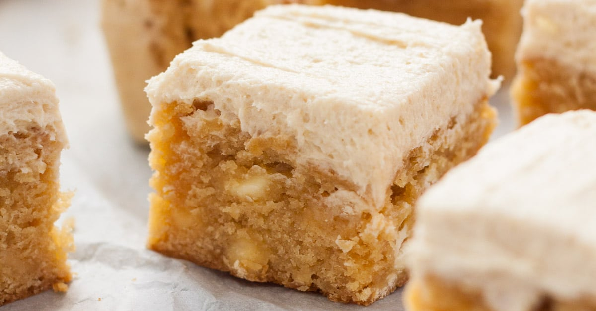 extreme closeup of a frosted blondie showing the inside texture and creamy frosting.
