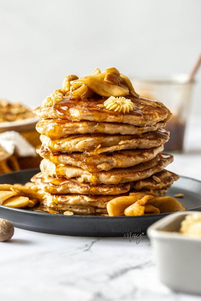 A tall stack of pancakes topped with butter and slices of cooked apples