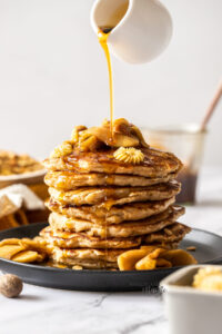 A stack of pancakes topped with apples with maple syrup being drizzled over the top