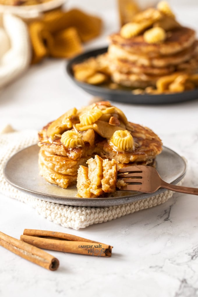 A stack of 3 pancakes on a grey plate topped with cooked apples and a bronze fork on the side