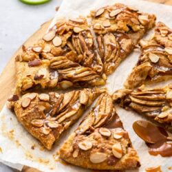 A crostata filled with apple and drizzled with caramel sauce on a wooden board with slices of apple in the background