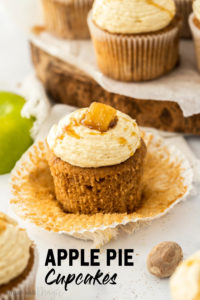 A closeup of an apple pie cupcake with the paper peeled away showing the texture of the cake. It sits on a marble worktop