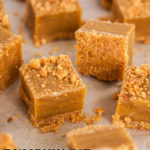 Numerous squares of pumpkin fudge on a white background