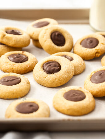 A batch of cookies with chocolate centres on a sheet of baking paper in a baking tin.