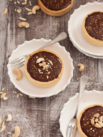 Nutty Caramel Chocolate Tarts - Almonds & cashews wrapped in caramel, fill a thin tart shell topped with Chocolate Ganache #nuts #baking