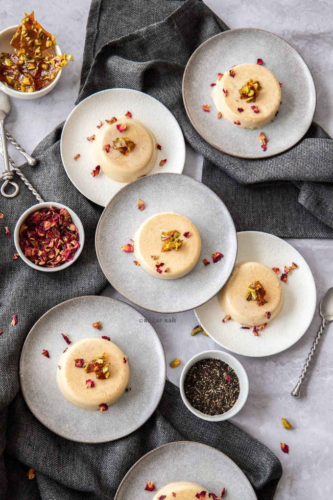 6 dessert plates on a table with panna cotta on each - top down view