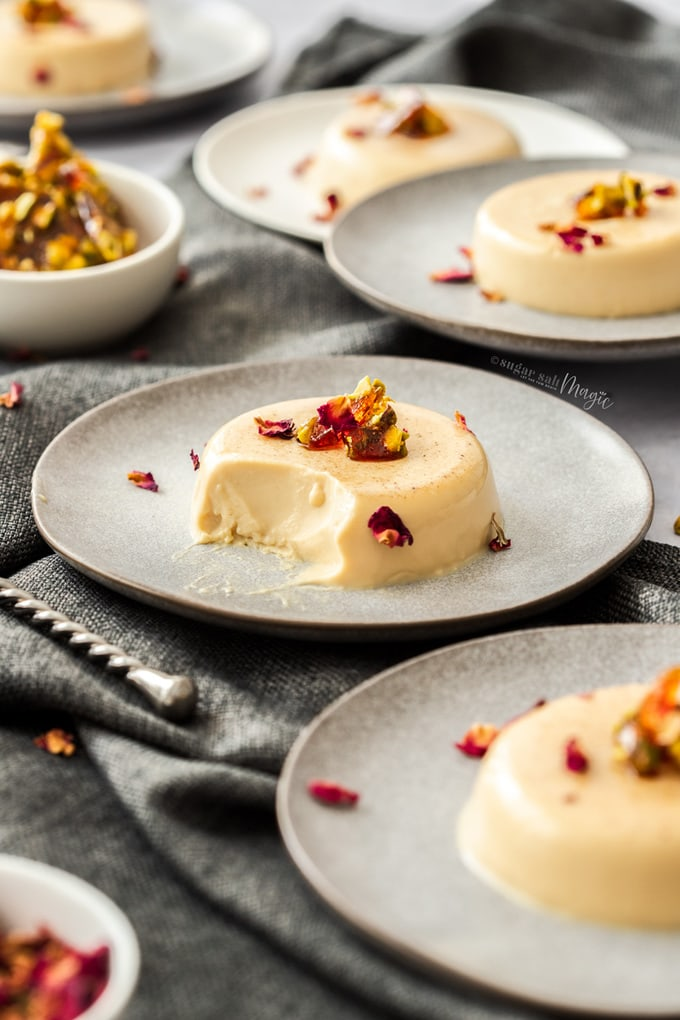 A panna cotta on a grey plate topped with toffee pieces and rose petals with a spoonful already taken