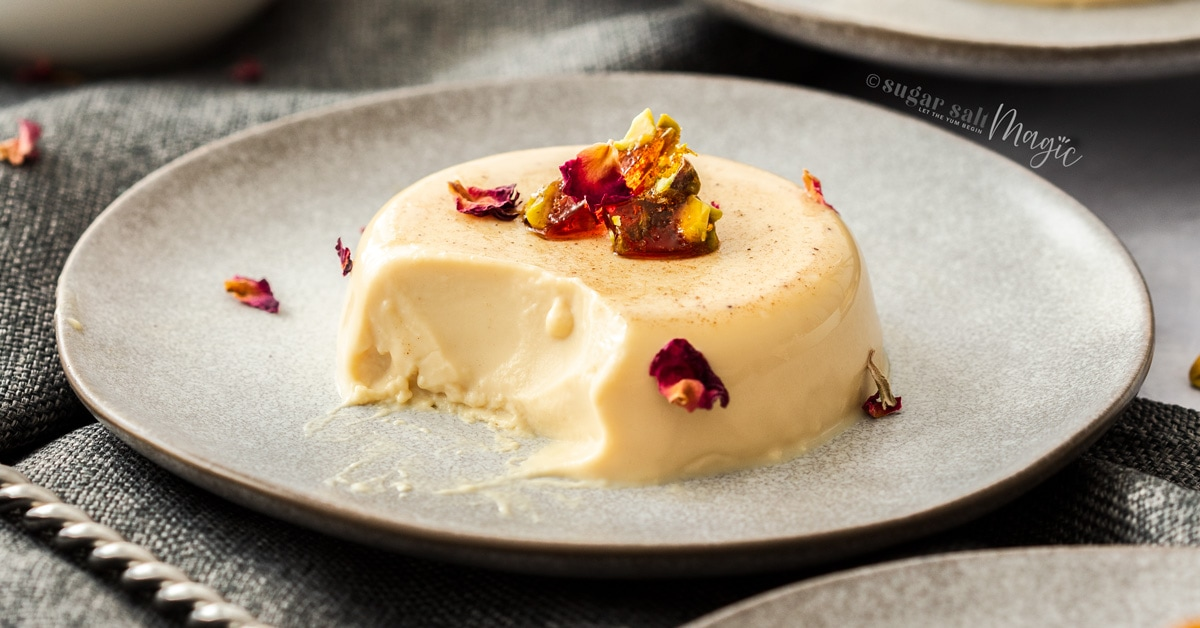 A chai panna cotta on a grey plate topped with toffee pieces and rose petals