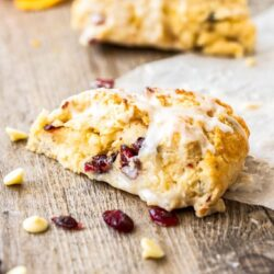 Closeup of a cranberry scone sitting on a wooden board