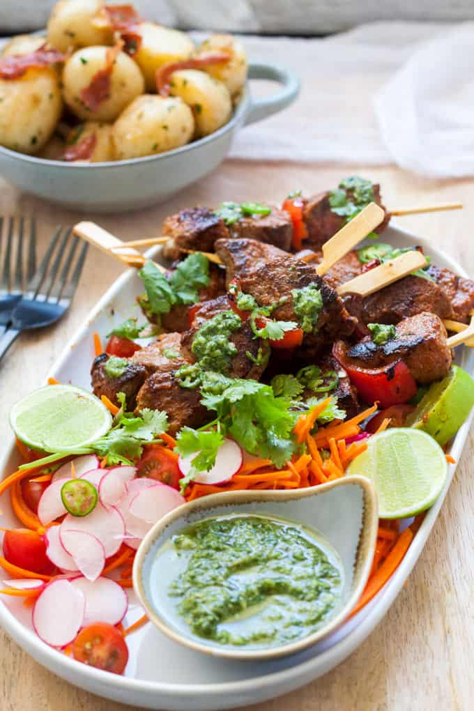 Easy to make beef shish kebabs on a platter with salad and mojo verde. Potatoes in the background