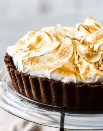 Closeup front on shot of a chocolate meringue pie on a black glass plate and black stand