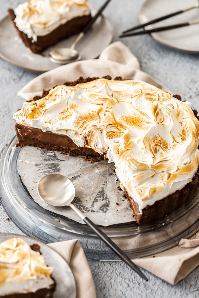 A chocolate meringue pie on a black glass plate with some slices already cut out. A black and silver spoon sits on the side of the plate