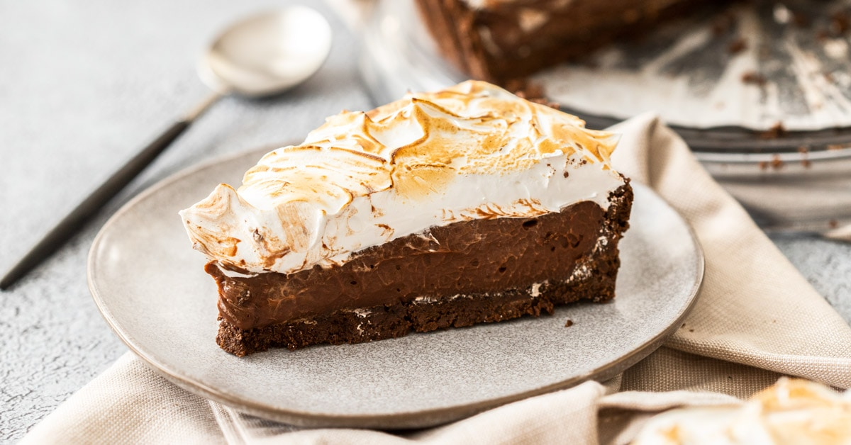 A slice of chocolate meringue pie on a grey plate sitting on a tan napkin