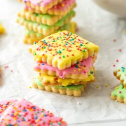 different coloured iced cookies covered in sprinkles on a sheet of baking paper