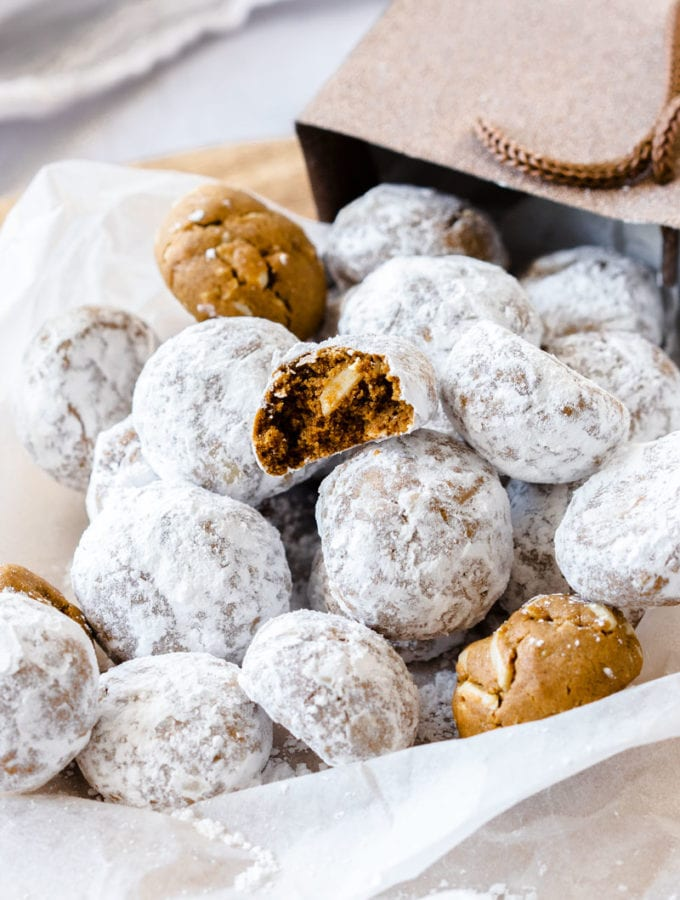 A pile of gingerbread flavoured snowball cookies, tumbling out of a gift bag onto a piece of white baking paper