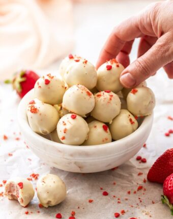 A batch of white chocolate truffles in a small white bowl with a hand reaching into pick one up