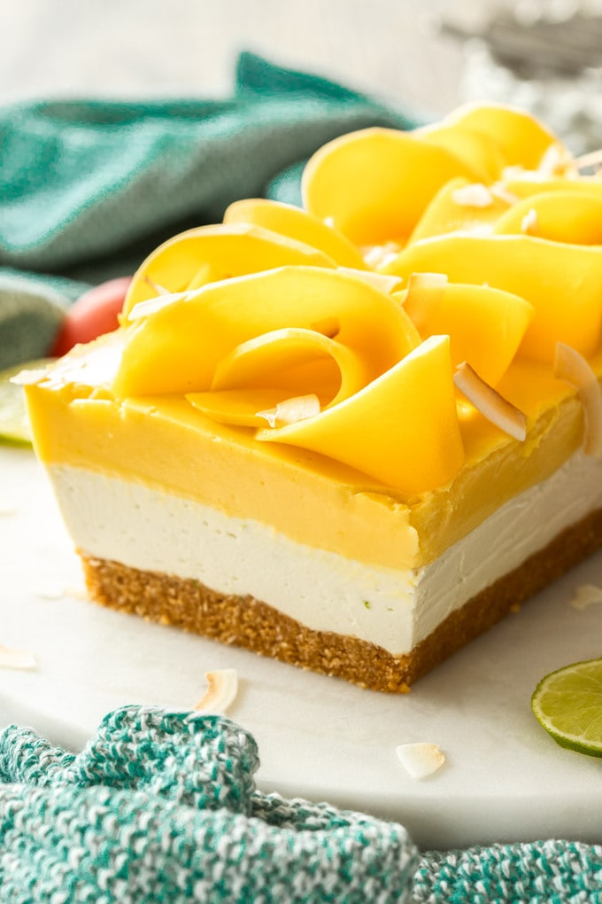 Close up of a 3-layer dessert topped with slices of mango and coconut chips.
