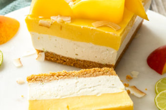 A dessert with 3 layers in a loaf shape on a marble cake plate. Topped with slices of mango.