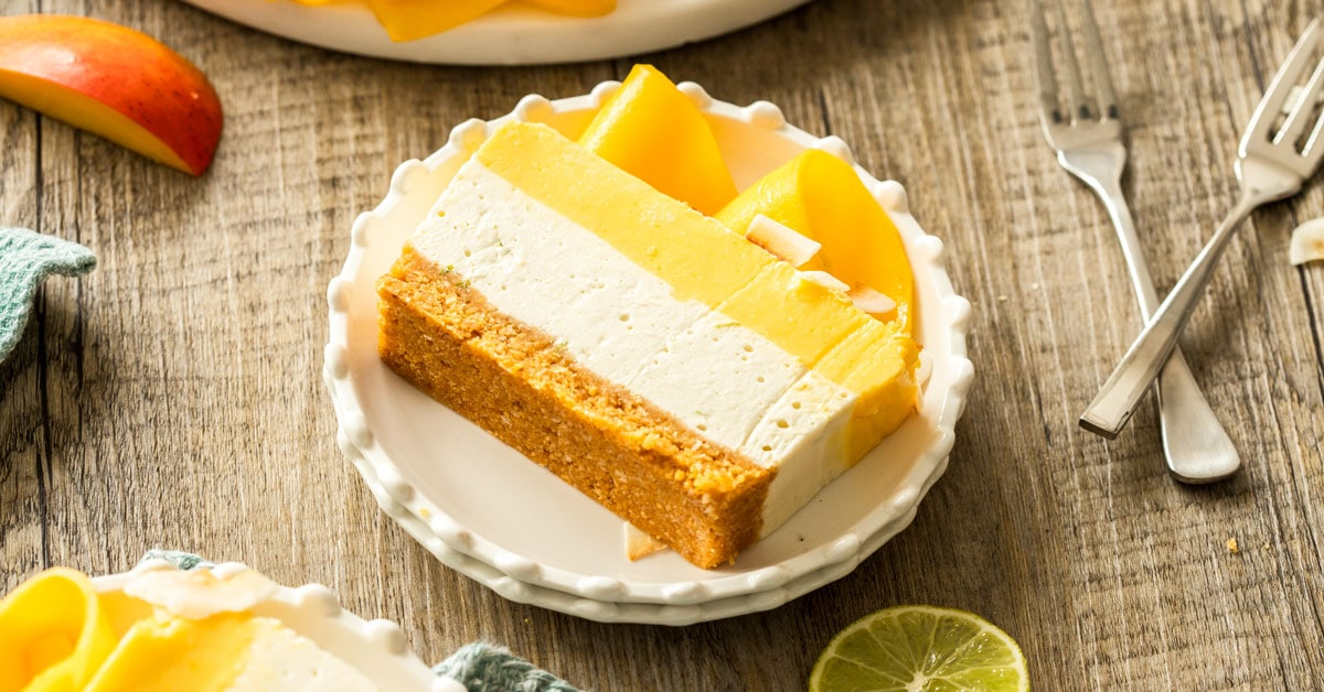 Slices of mango cococonut cheesecake on white plates, with forks around and slices of lime.