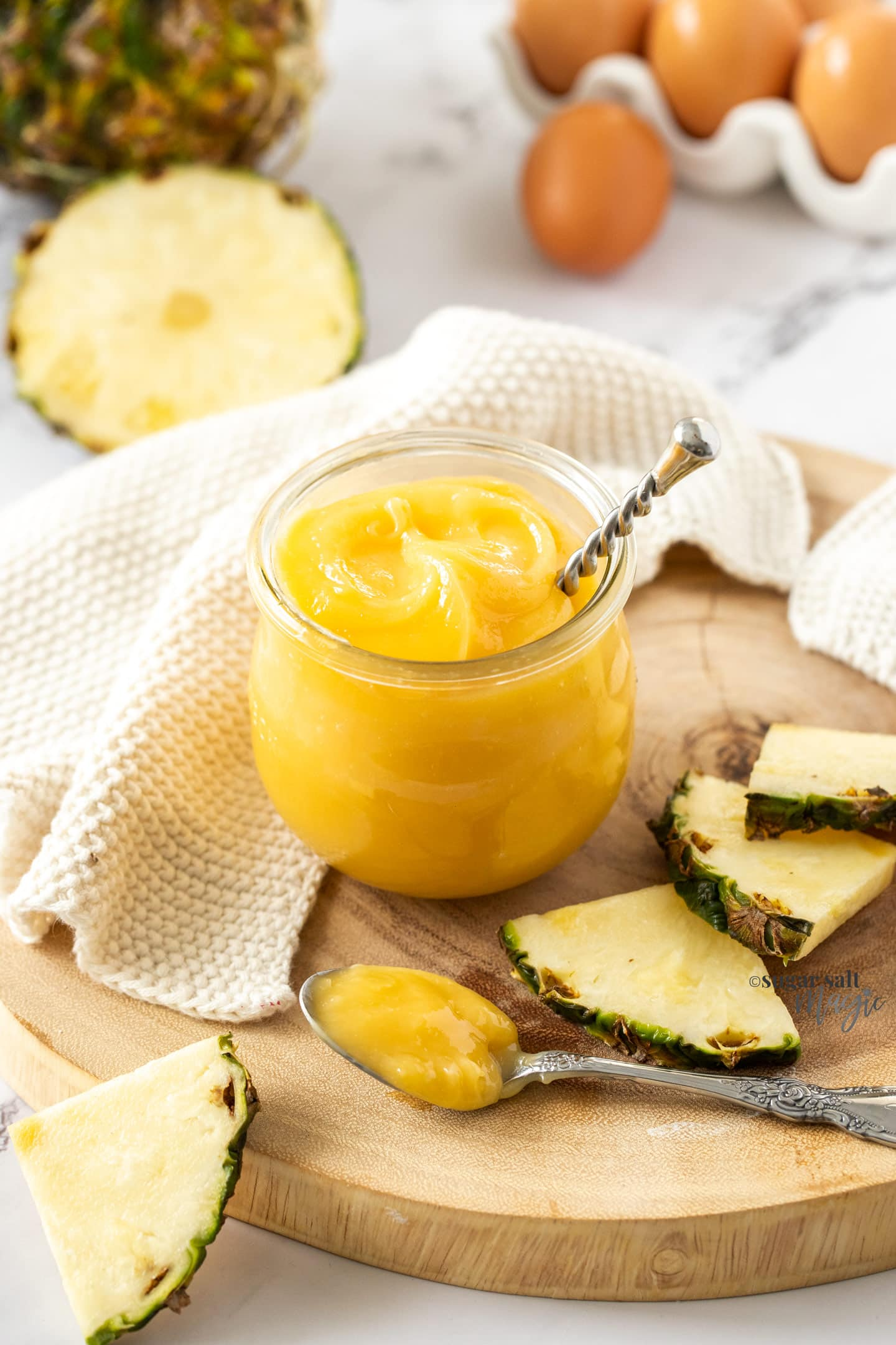 Pineapple curd in a glass jar with a spoon sticking out