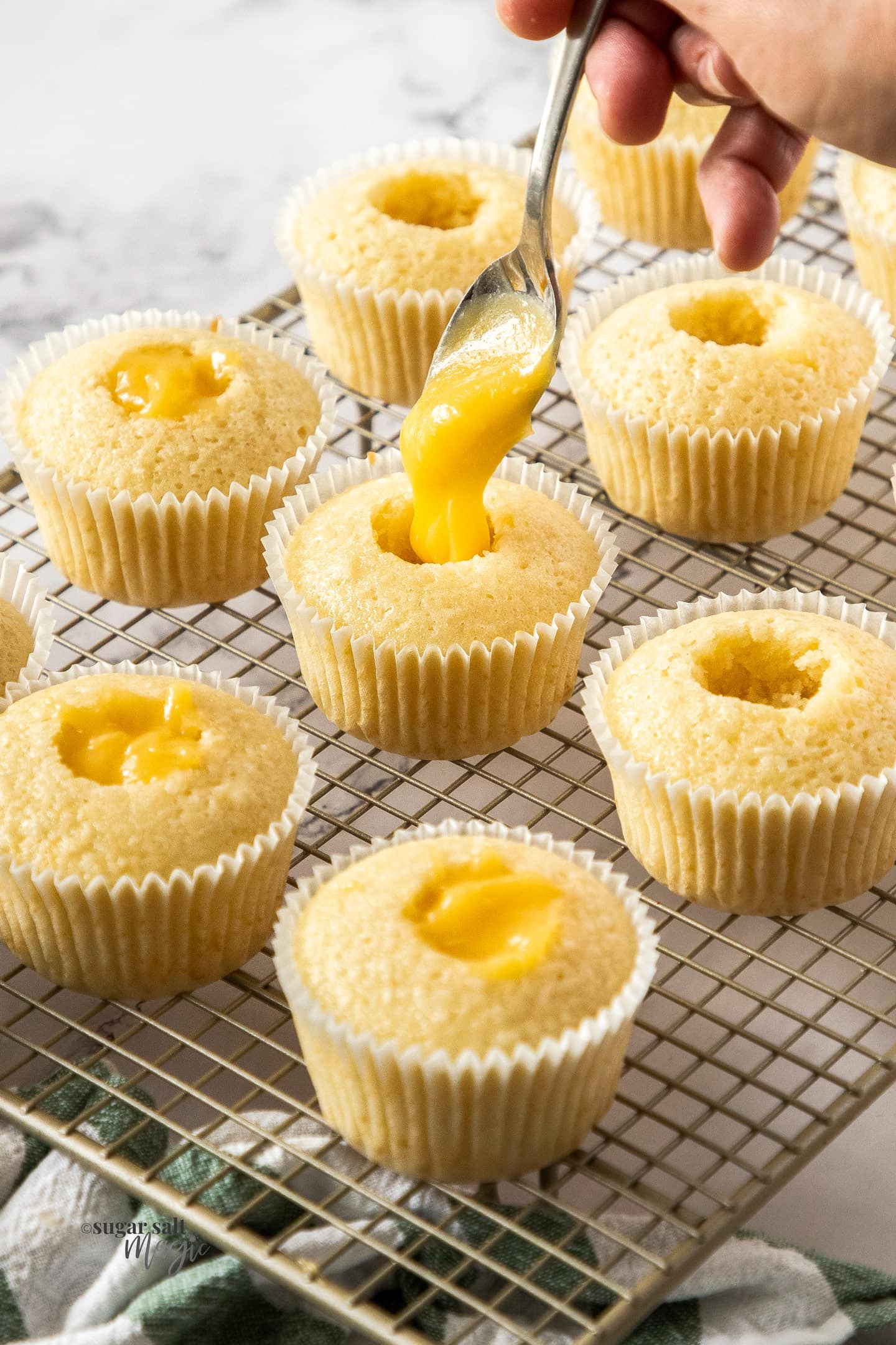 Pineapple curd being spooned into the centre of cupcakes