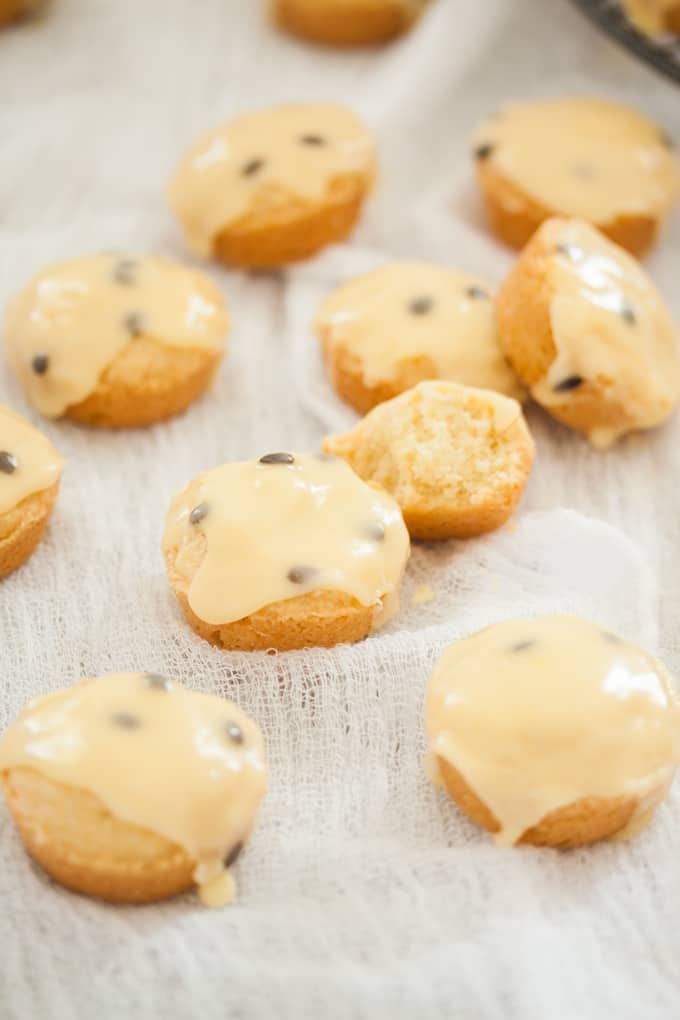 A batch of small round vanilla shortbreads with passionfruit icing over the top