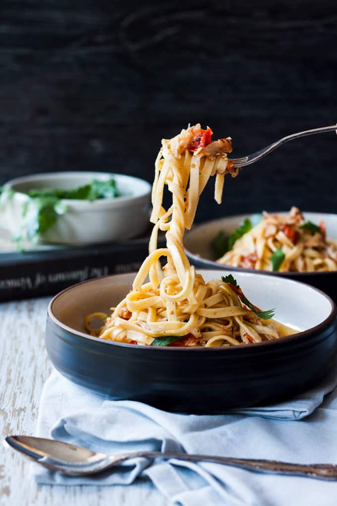 Two bowls of linguine with some pasta being lifted by a fork