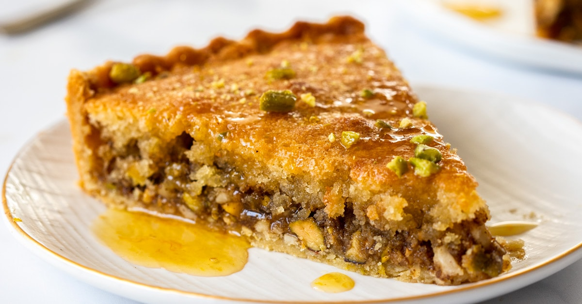 A slice of baklava tart on a white plate with syrup drizzling down the side