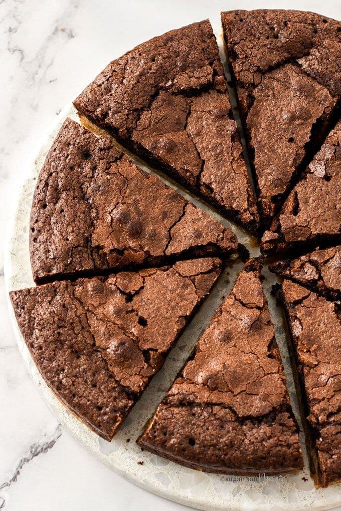 Top down view of 8 slices of brownie pie on a white marble platter