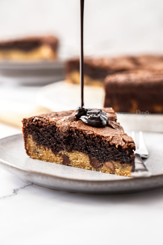 A slice of brownie pie on a grey plate with chocolate sauce being poured on top